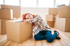 Woman sleeps on carton box, moving to new house Stock Images