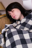 A woman sleeps in covered plaid Stock Image