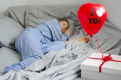 Woman sleeps in pajamas, a gift on the bed. Valentine`s Day. Royalty Free Stock Photo