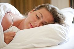 Woman sleeps on a snow-white bed Royalty Free Stock Photos