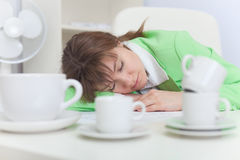 Woman sleeps on workplace with coffee cups Stock Photo