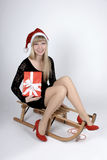 Woman on a sleigh with gift Royalty Free Stock Photo