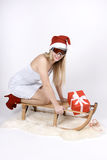 Woman on a sleigh with gift Royalty Free Stock Images