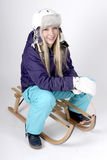 Woman on a sleigh. Young blond woman with skiing suit and helmet on a sleigh Stock Photography