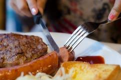Woman slice sausage steak set on white dish royalty free stock photography