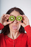 Woman with sliced kiwis on eyes and sticking out tongue. Face portrait of adult brunette woman with red sweater holding two halves of cut kiwi on her eyes, and stock images