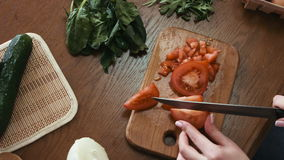 Woman slices a tomato for a salad on a kitchen wooden table,  vegetables, greenery and other ingredients are lying stock video footage