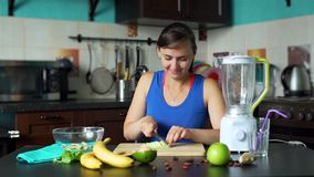 Woman Slicing Avocado on a Board in the Kitchen. Smiling Young Woman Slicing Fresh Avocado on a Cutting Board in the Kitchen. Making a Smoothie Process. Healthy stock footage