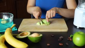Woman Slicing Avocado on a Cutting Board. In Slow Motion. Close Up. Process of Making a Homemade Smoothie. Healthy Lifestyle, Weight Loss Food and Nutrition stock video footage
