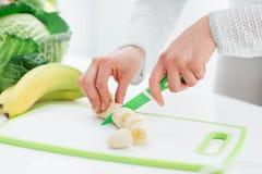 Woman slicing a banana Royalty Free Stock Photos