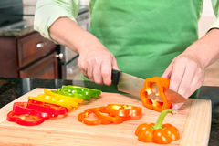 Woman Slicing Bell Peppers. A woman slicing bell peppers prepares the vegetables as meal ingredients Royalty Free Stock Images
