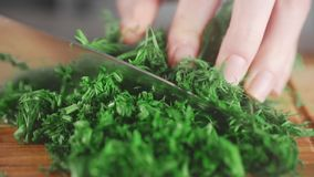 Woman is slicing greens on the wooden board in the kitchen, greens from own garden, summer vitamins, useful materials. Woman is slicing greens on the wooden stock video footage