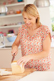 Woman Slicing Loaf Of Bread In Kitchen Royalty Free Stock Image