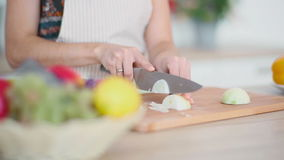Woman is slicing onion stock footage