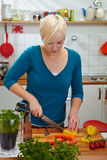 Woman is slicing paprika Royalty Free Stock Image