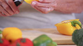 Woman slicing a peppper. Woman slicing a yellow pepper on a wooden board stock video