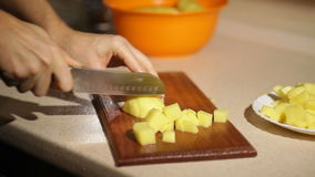 Woman is slicing potatoes on a wooden board stock video footage