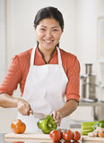 Woman Slicing Produce. A woman is slicing produce in her kitchen.  She is smiling at the camera.  Vertically framed shot Stock Photo
