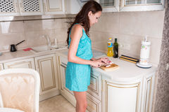 Woman Slicing Raw Meat at the Kitchen. Three Quarter Shot of a Young Woman Slicing Raw Meat to Cook for Lunch at the Home Kitchen Stock Images
