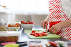 Woman Slicing strawberries on kitchen table. Royalty Free Stock Photo
