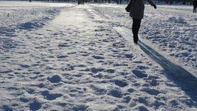 Woman slide frozen ice field lake winter evening sulight shadows stock video footage