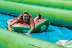 Woman Slides Down Giant Slip And Slide In Innertube. Atlanta, GA, USA - July 15, 2017:  A young woman laughs as she travels down a giant slip-and-slide in an Royalty Free Stock Photo