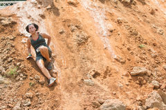 Woman Slides Down Slick Dirt Hill In Obstacle Course Race Royalty Free Stock Photography