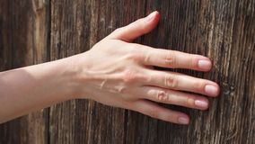 Woman sliding hand against old wooden door in slow motion. Female hand touch rough surface of wood
