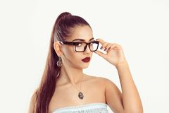 Woman with slight smile holding eye glasses stock photo
