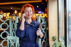 A woman with a slight smile is talking on the phone with a tablet in her hand. Adult woman, aged, red-haired, in a blue dress and glasses with a small smile Royalty Free Stock Images