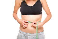 Woman slim stomach with measuring tape around it Royalty Free Stock Photography