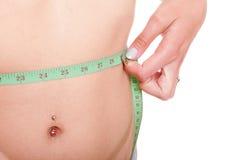 Woman slim stomach with measuring tape around it Royalty Free Stock Photos