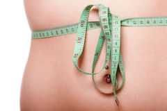 Woman slim stomach with measuring tape around it Royalty Free Stock Image
