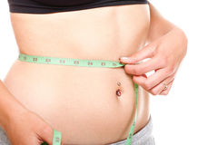 Woman slim stomach with measuring tape around it Royalty Free Stock Images