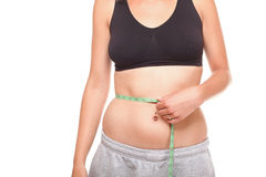 Woman slim stomach with measuring tape around it Royalty Free Stock Photos