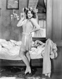 Woman in a slip and combing her hair posing sexily in her bedroom Stock Photography