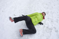Woman slipped on a snow and ice. Risk of accidents in winter. Mid aged woman is slipping and falling on footpath, street covered with snow and black ice Stock Images