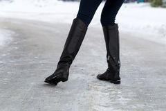 Woman slips on slippery road covered with ice. Concept of injury risk in winter. Close shot Stock Photo