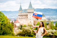 Woman with slovak flag near the castle. Young female tourist holding slovak flag with Bojnice castle on the background in Slovakia. Promoting tourism in Slovakia royalty free stock photo