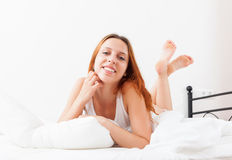 Woman is slowly waking up in her bed Stock Images
