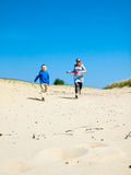 Woman and small boy running in dunes Royalty Free Stock Photo