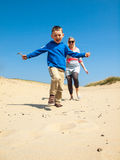 Woman and small boy running on a sand dune Royalty Free Stock Photos