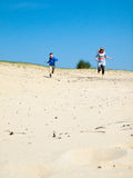 Woman and small boy running through sand dunes Royalty Free Stock Photo