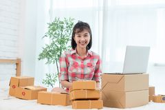 Woman small business owner, business start up conceptual, young. Entrepreneur work with laptop sell product on line shop in bedroom stock photography