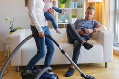 Woman with small child doing housekeeping while man sitting in couch royalty free stock image