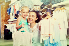 Woman with small child in kids apparel boutique. Happy women with small child holding clothes in kids apparel boutique Stock Image