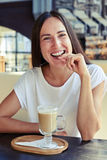 Woman with small cookies and cappuccino. Joyful woman with small cookies and cappuccino in the cafe Royalty Free Stock Photography