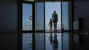 A woman with a small daughter go through the glass doors of the hotel to the promenade with a beautiful view of the sea. stock footage