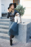 Woman with small dog in city street. Royalty Free Stock Images