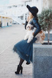 Woman with small dog in city street. Stock Photo